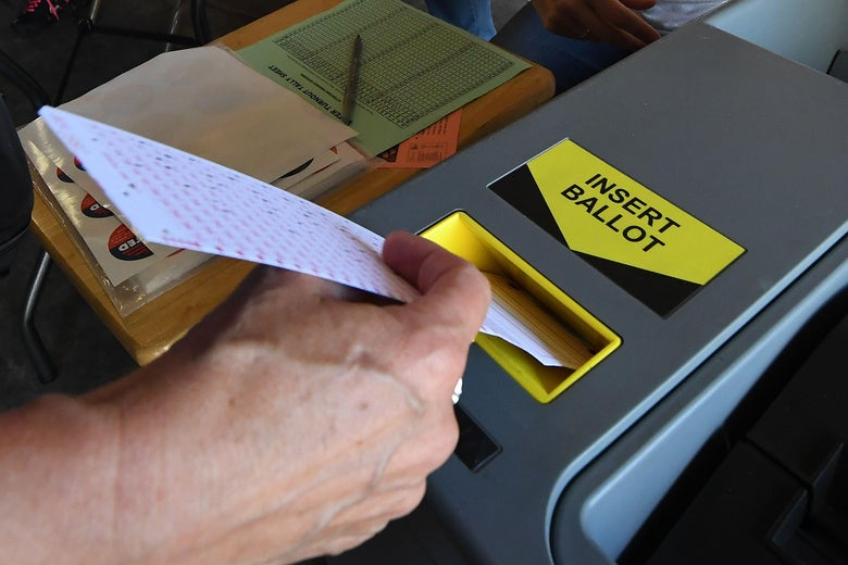 A woman inserts her ballot into the machine.