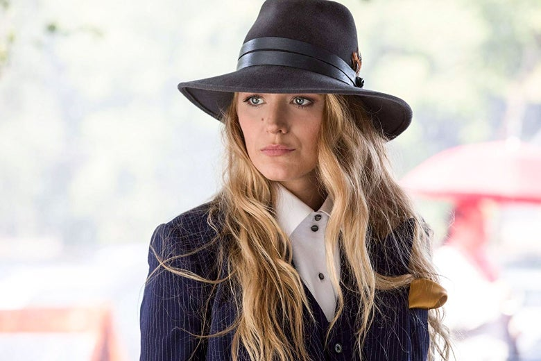 Blake Lively wears a grim expression, a suit, and a fedora in this still from A Simple Favor