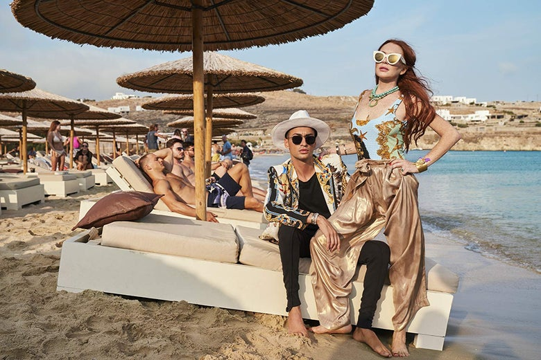 On the sand at Lindsay Lohan's Beach Club in Mykonos, Panos sits, wearing sunglasses and a hat, and Lindsay stands beside him, wearing a bathing suit, shiny pants, and sunglasses, looking triumphant.