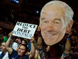 A supporter of Ron Paul waves his portrait during the Sunday rally in Tampa.