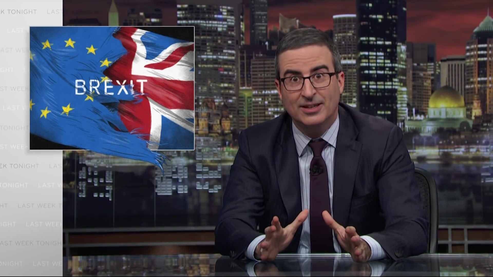 "John Oliver at his desk, in front of a graphic reading ""BREXIT."""
