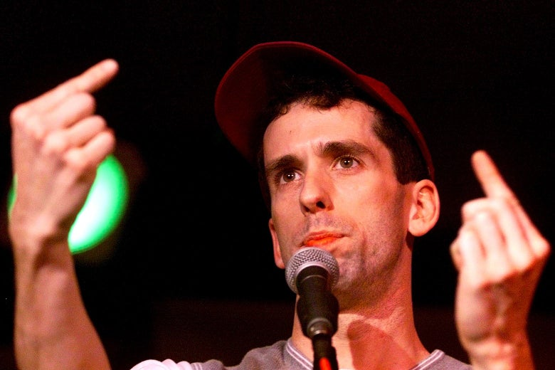 Dan Savage, wearing a red baseball cap and behind a microphone, points both index fingers updward.
