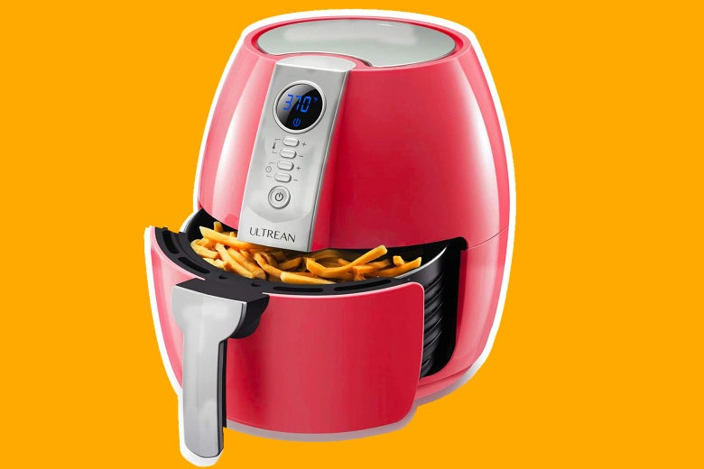 A red air fryer with crispy fries exposed in the open drawer.