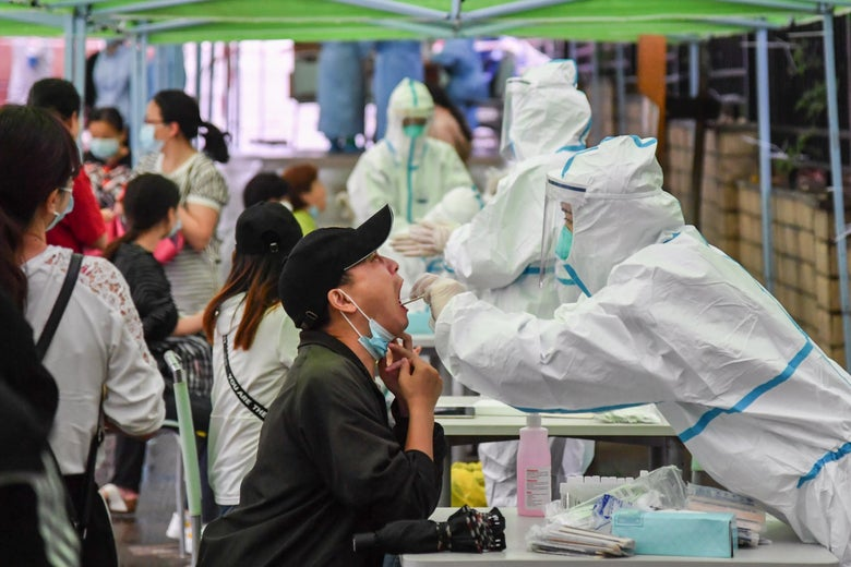 A man, sitting down, opens his mouth wide as a medical worker in personal protective equipment takes a swab sample from his throat. Others wait in line behind the man.