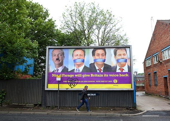 A man walks past a defaced UKIP poster on May 22, 2014 in Sheffield, England.
