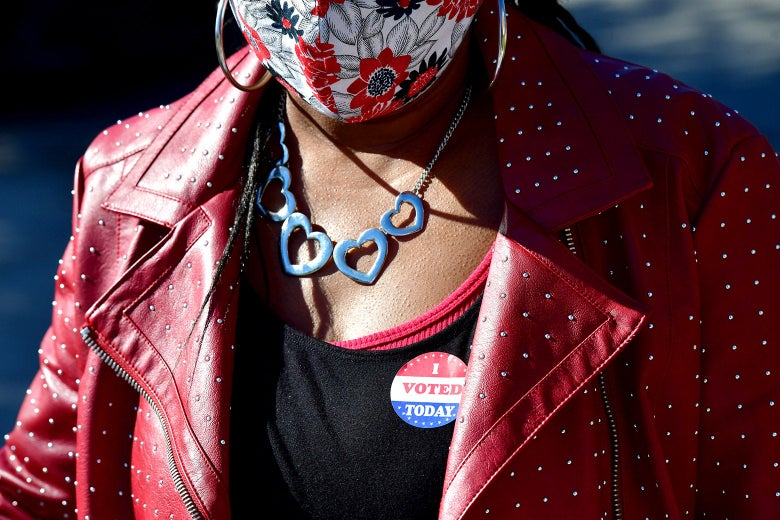 A Black woman in a red leather jacket with an I voted sticker and a mask on.