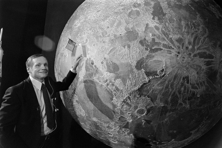 Neil Armstrong poses next to a large picture of the moon that has a tiny U.S. flag sticking out of it.
