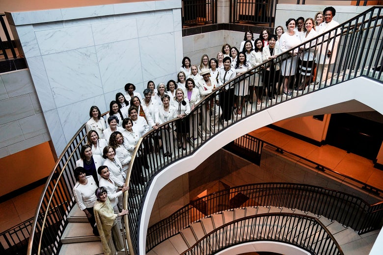 Nancy Pelosi and congresswomen wearing white pose for a photo on a spiral staircase.