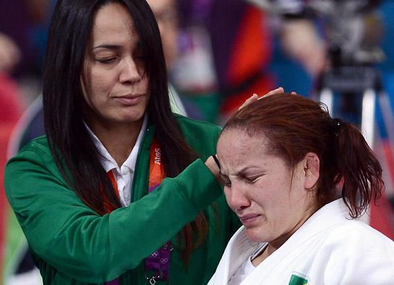 Brazil's Maria Portela leaves with her coach Campos Rosicleia after losing