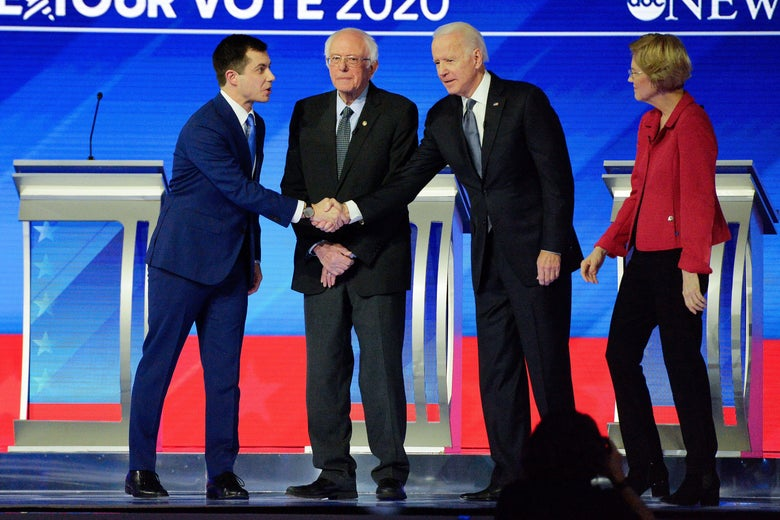 Democratic presidential hopeful former Mayor of South Bend, Indiana, Pete Buttigieg shakes hands with former Vice President Joe Biden as Vermont Sen. Bernie Sanders and Massachusetts Sen. Elizabeth Warren look on during the eighth Democratic primary debate of the 2020 presidential campaign season at St. Anselm College in Manchester, New Hampshire, on February 7, 2020.