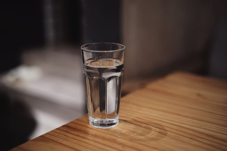 A glass of water on the edge of a table.