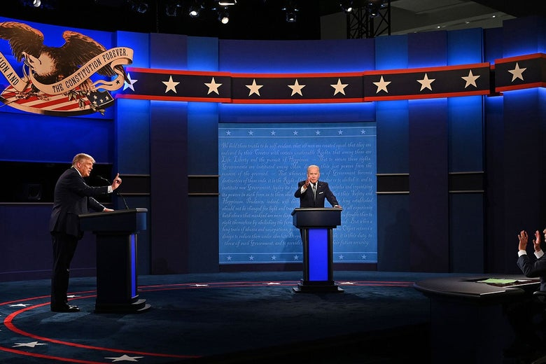 Biden, seen from a distance, gestures directly toward the camera while Trump, to the left of the frame, gestures toward the moderator's table.