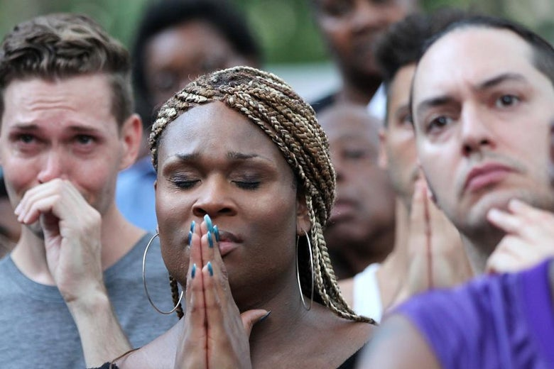 A woman in a crowd holds her hands up to her face as if in prayer.