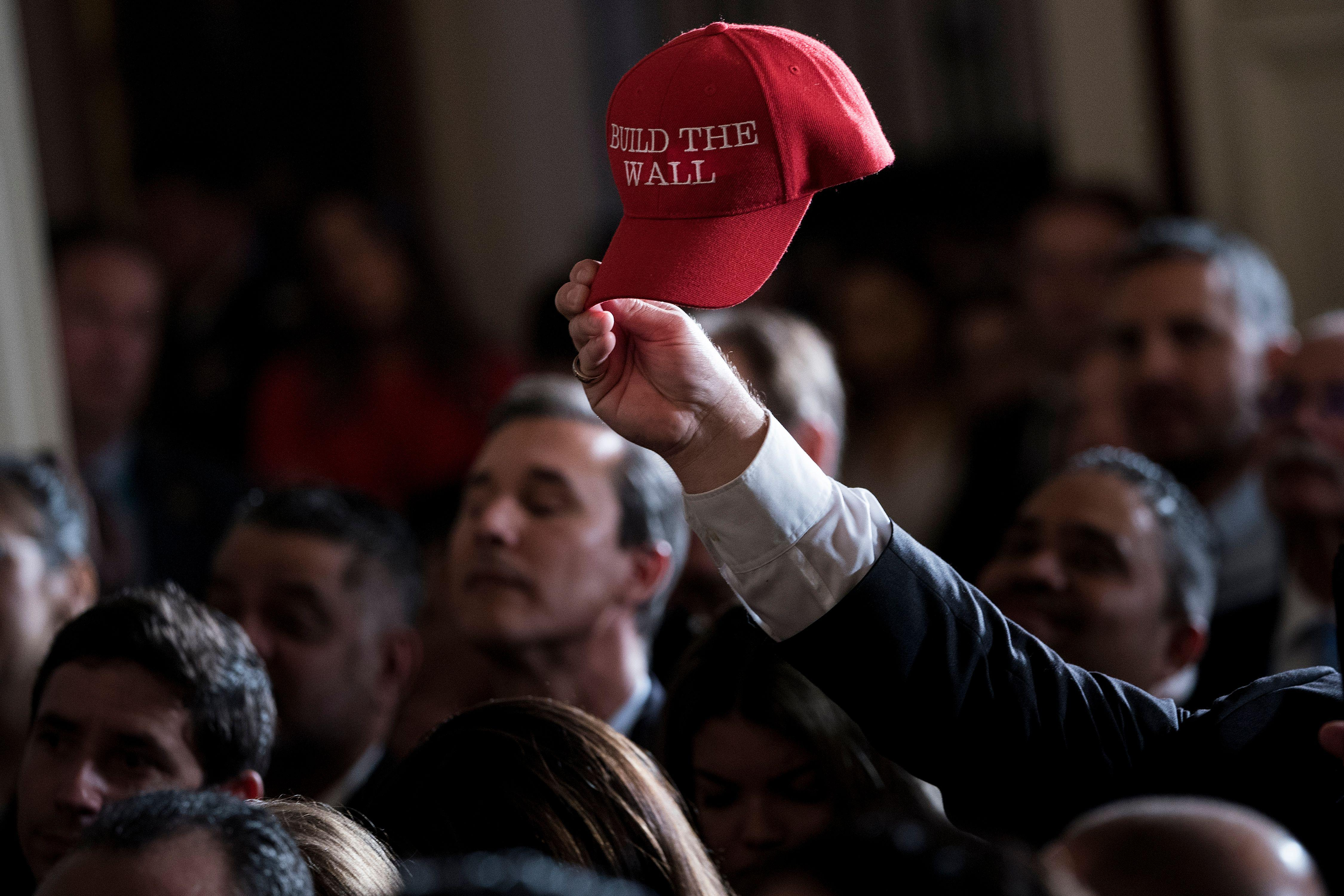 Fredy Burgos, of Virginia, holds up a 'Build the Wall' hat while waiting with others for a Hispanic Heritage Month event in the East Room of the White House