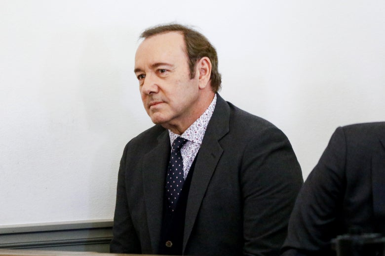 Kevin Spacey, in a gray three-piece suit, sitting at the defense table in a Massachusetts courtroom.