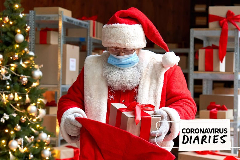 Man wearing a Santa Claus costume and surgical mask stands in a storeroom full of cardboard boxes with red bows on them. He is putting one such box in a large red sack. There's a Christmas tree in the background.
