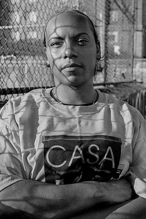 Dulce Infante stands in front of a fence with her arms crossed. Her shirt reads CASA.