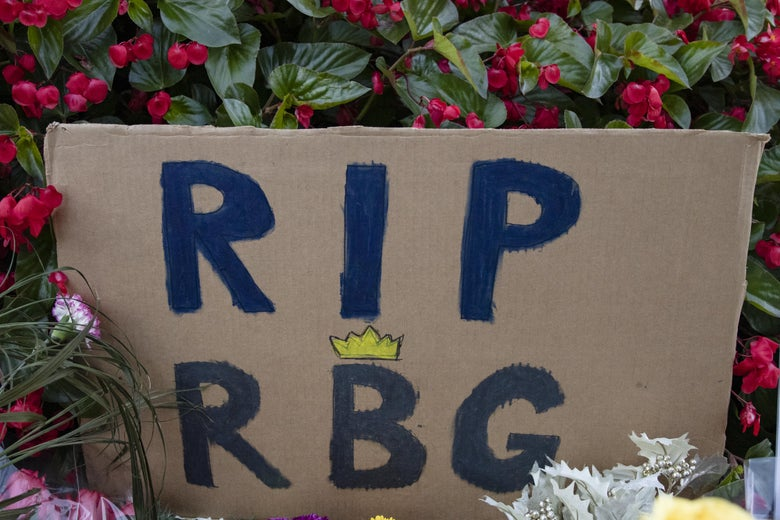 """A cardboard sign that reads """"RIP RBG,"""" amid flowers"""