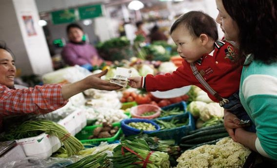 A woman asks her child to pay for vegetables at a food market in Shanghai, China on March 9, 2013.