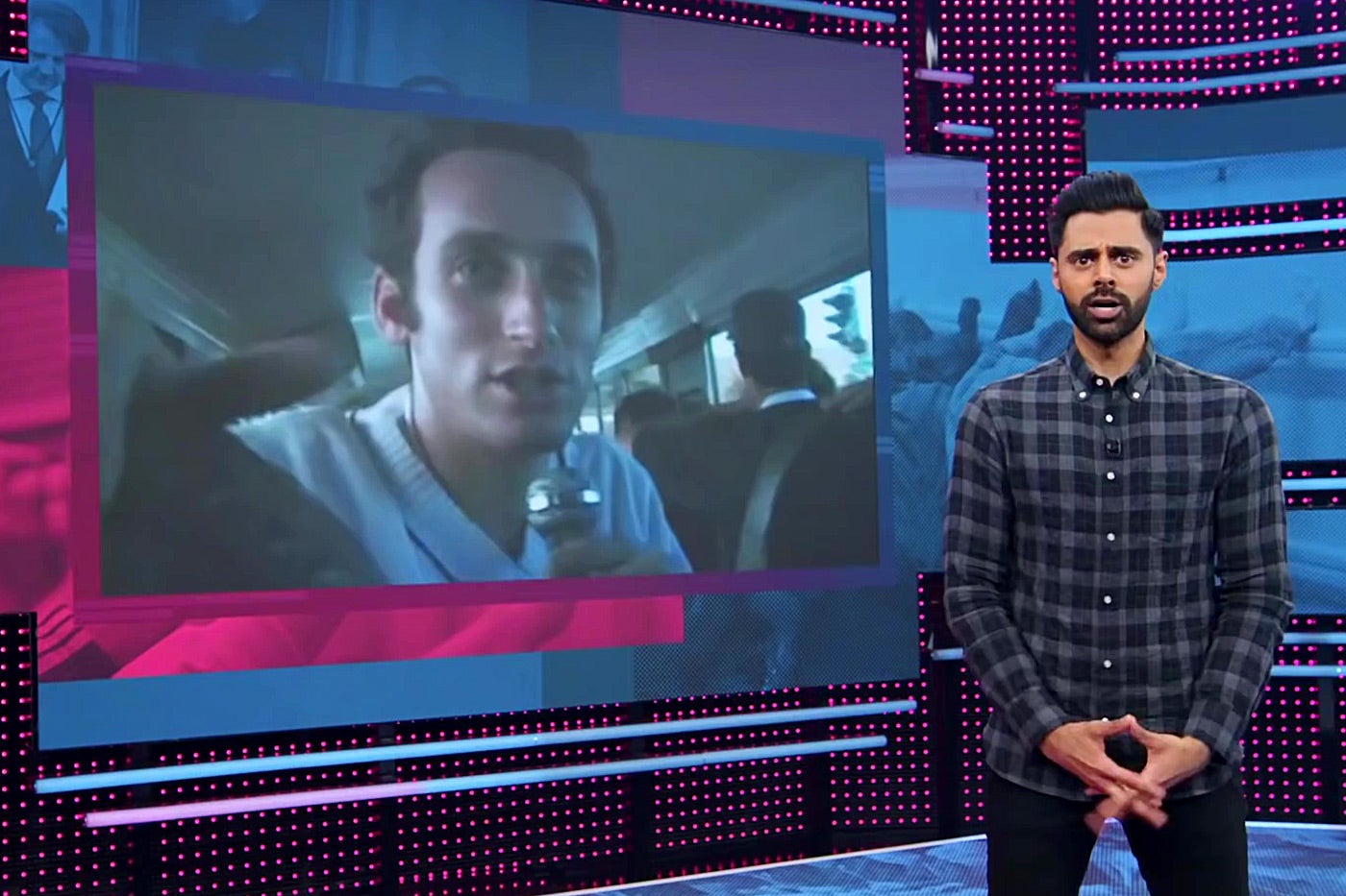 Hasan Minhaj in front of a photo of young Stephen Miller.