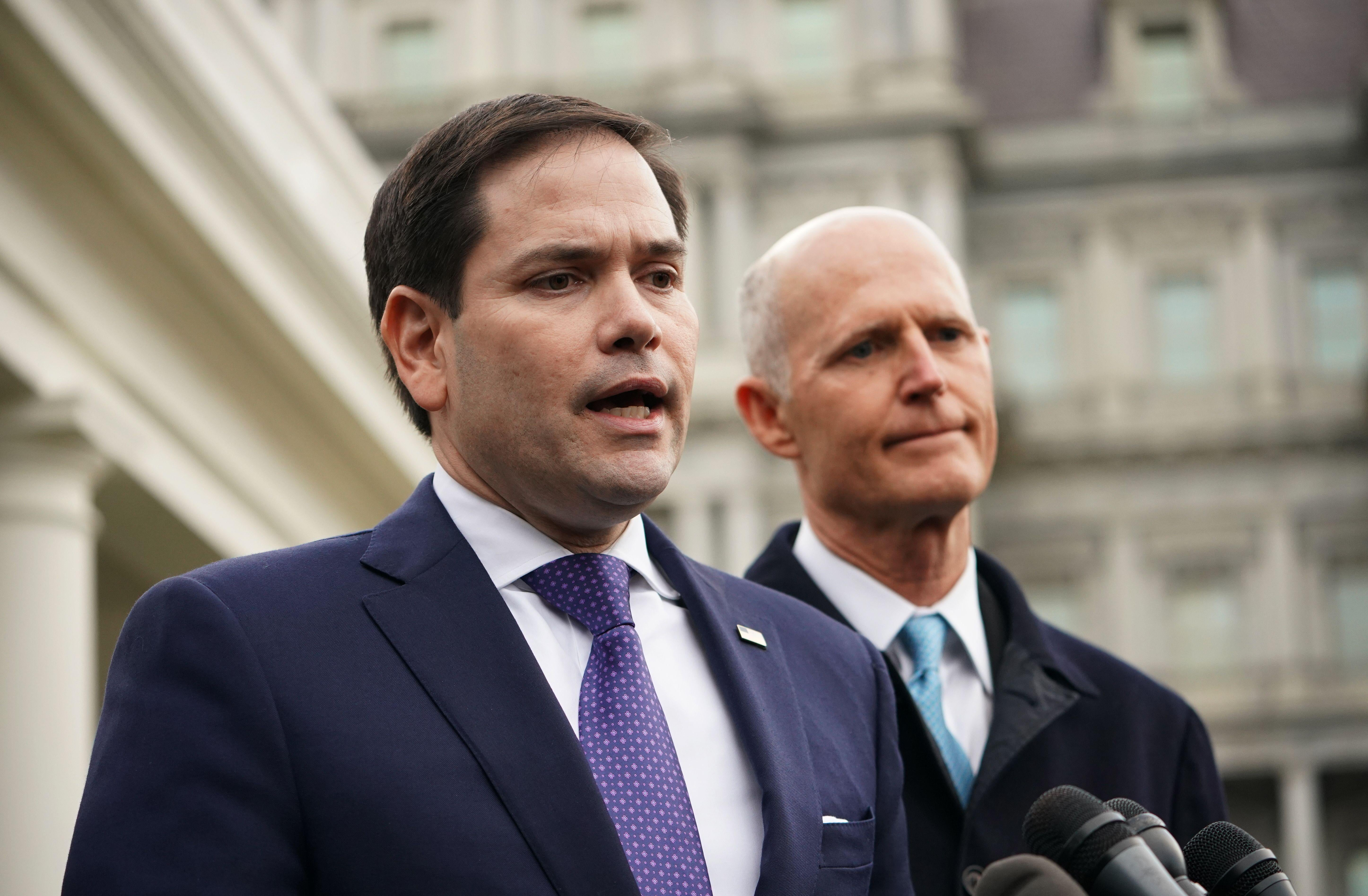 Marco Rubio speaks to reporters while Rick Scott stands by.