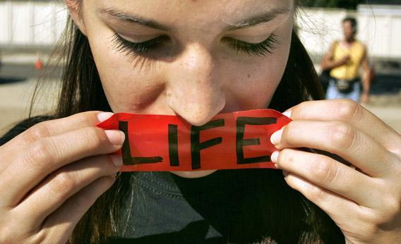 Abigail Brown of Phoenix, Arizona, puts a 'LIFE' sticker over her mouth while praying in front of the Supreme Court building/