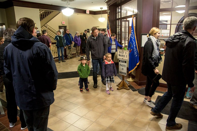 A presumed father stands with two young children while he waits in line to vote.