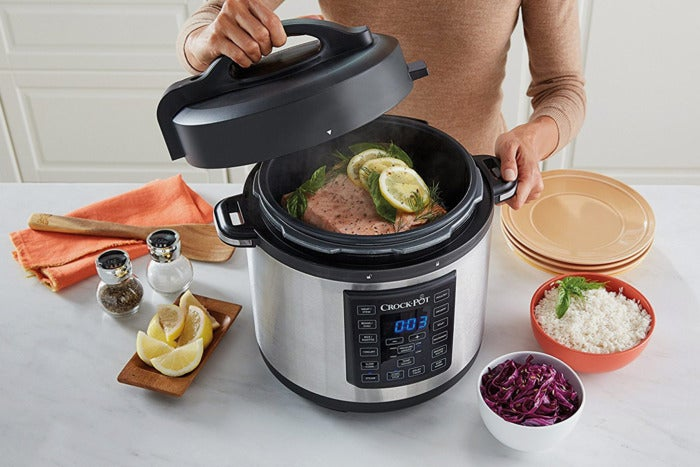 Woman opening a Crockpot to show fish cooking inside.