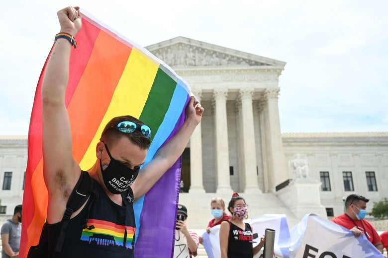 Man wearing a black mask and shirt with sunglasses on his head drapes holds a rainbow flag above his head in front of the Supreme Court.