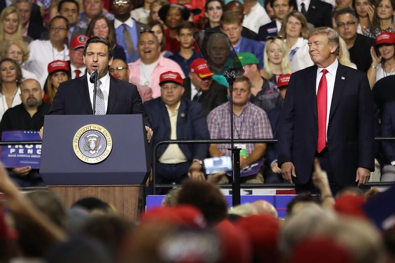 Ron DeSantis speaking at a lectern while Donald Trump watches from the side of the stage