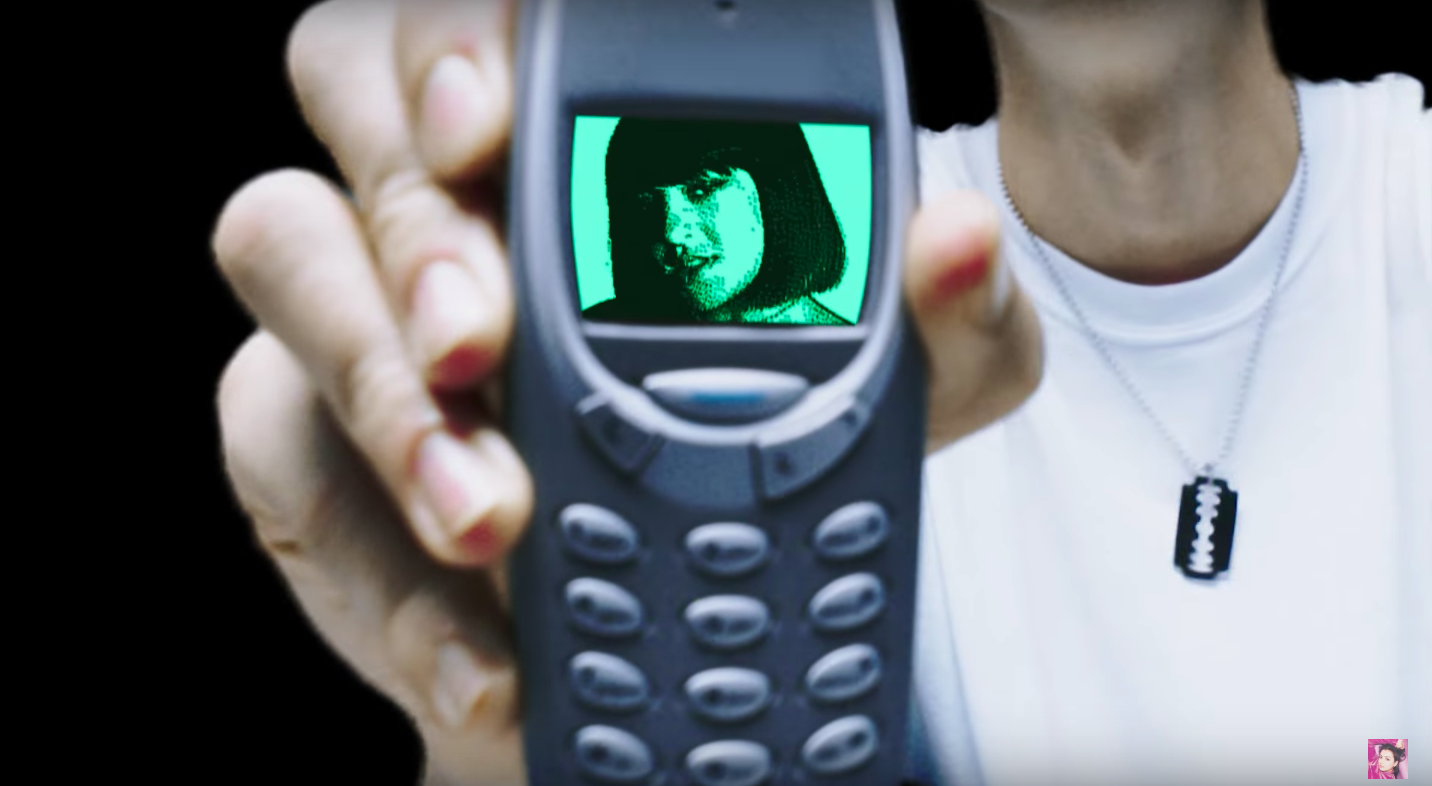 Charli XCX on a phone screen.