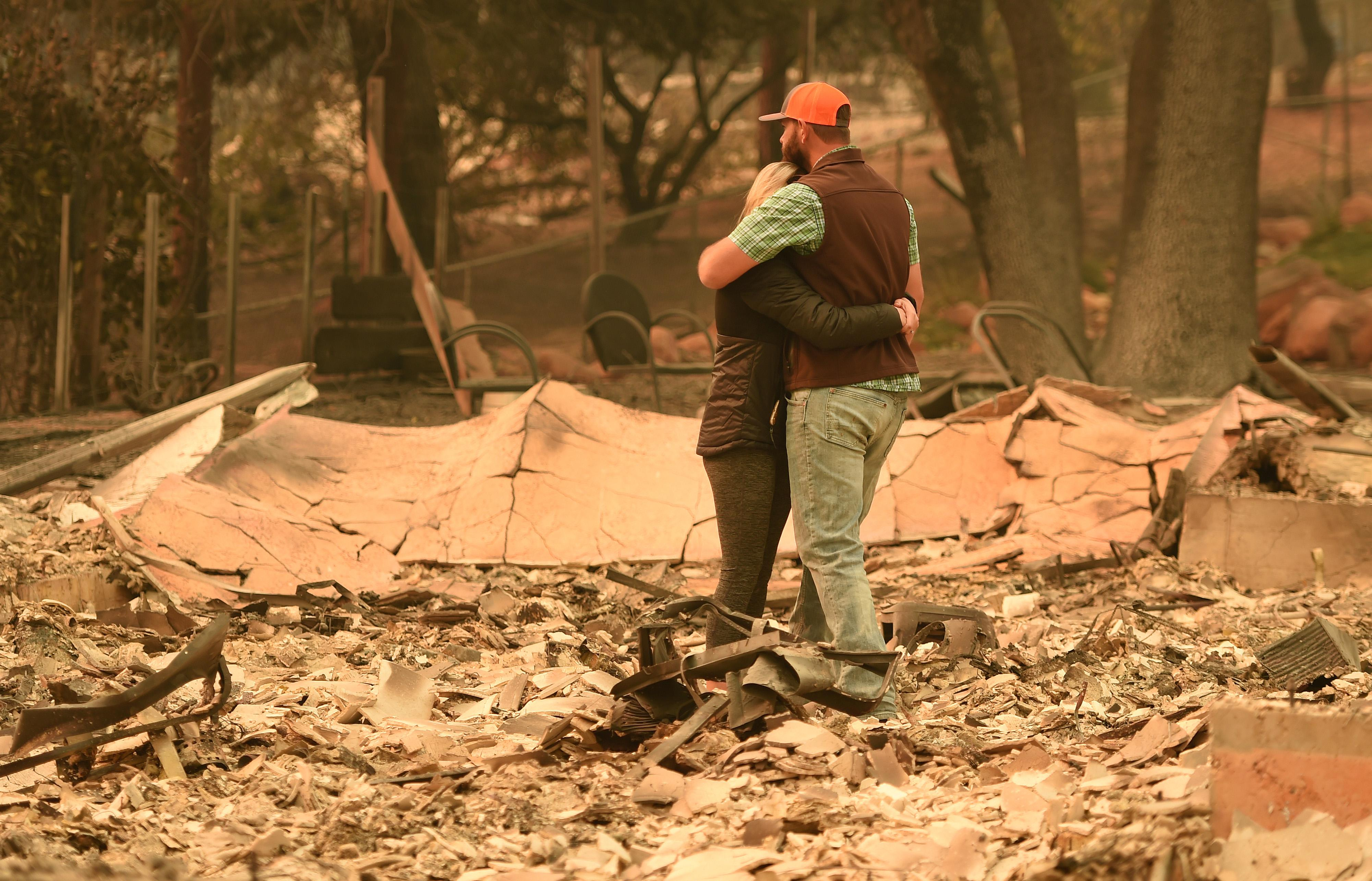 A couple embrace in the middle of the rubble of their home.