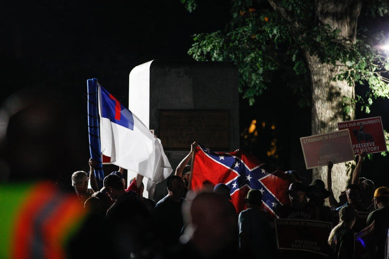 Pro-confederacy protestors hold up Christian Flags and Confederate flags inside a pen guarded by law enforcement where the 'Silent Sam' statue once stood.