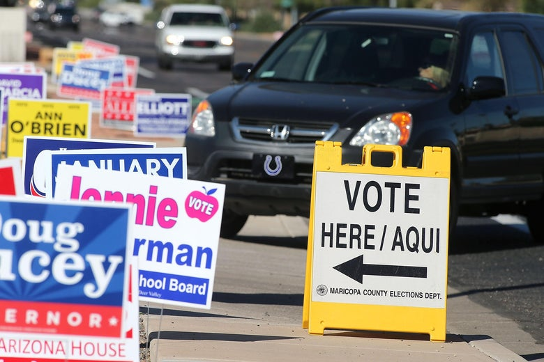 """A car drives by a """"VOTE HERE/AQUI"""" sign and a row of campaign signs for Doug Ducey and others."""
