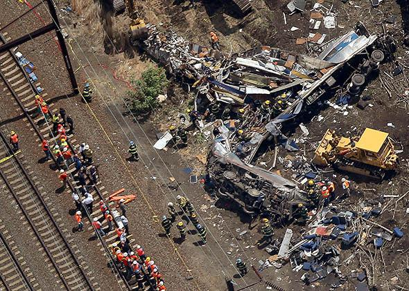 Investigators and first responders work near the wreckage of an Amtrak passenger train carrying more than 200 passengers from Washington, DC to New York that derailed.
