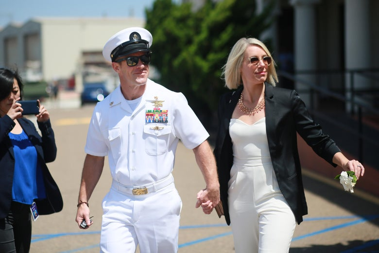 Edward Gallagher, wearing Navy dress whites, walks down the street with his wife.