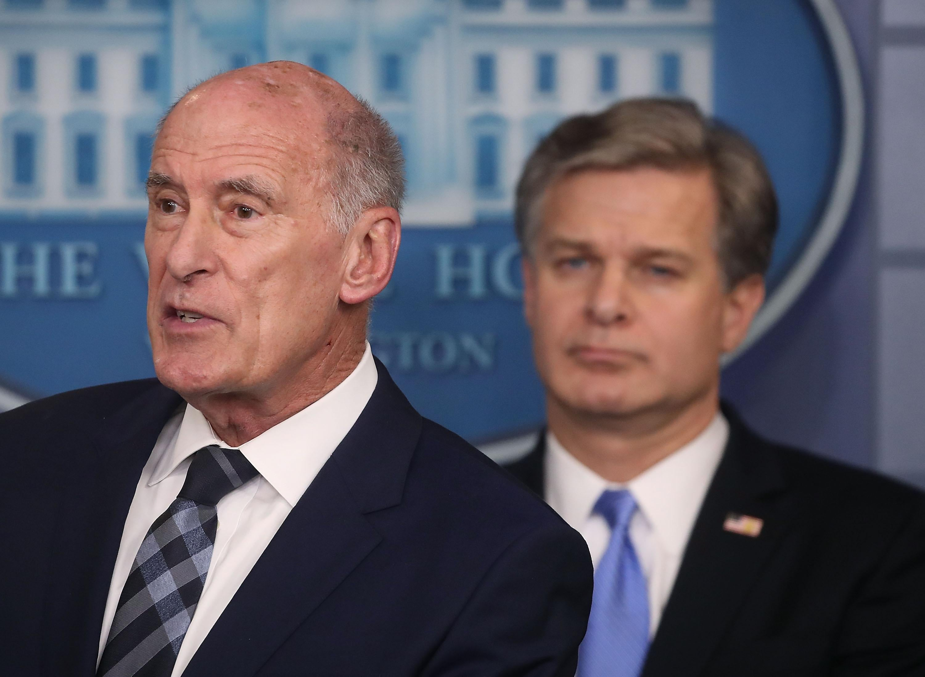 Dan Coats and Christopher Wray in White House briefing room.