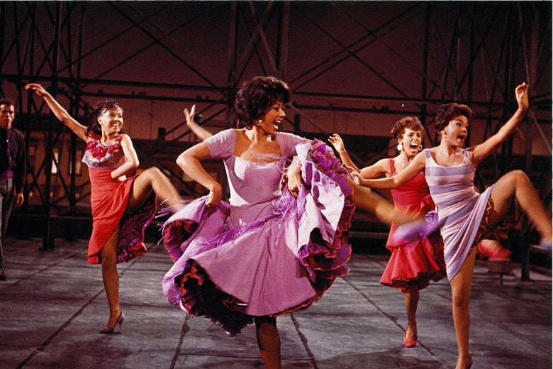 Rita Moreno leads a group of high-kicking women in brightly colored dresses.