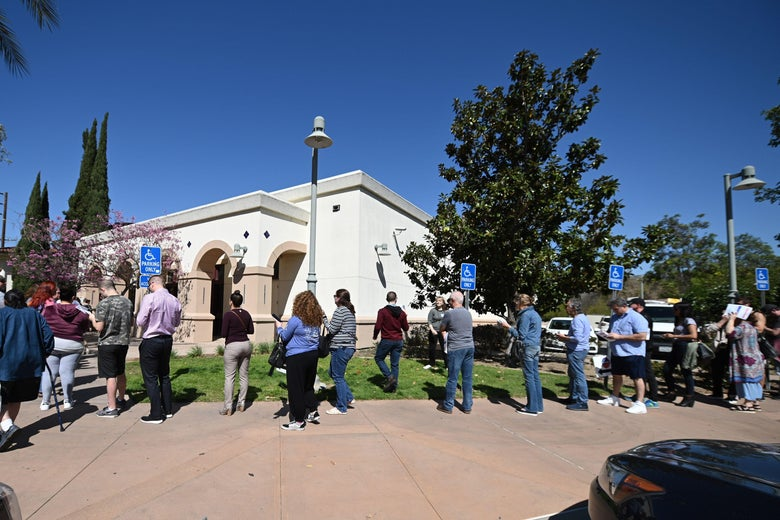 A long line of voters stand outside on a sunny day.