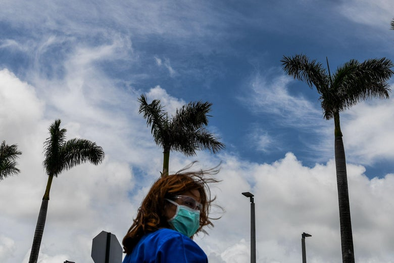 A healthcare worker in scrubs, a mask, and glasses stands before palm trees and a blimp in the sky.