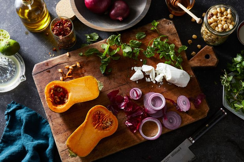 On a cutting board, a bright orange squash sliced in half, tendrils of purple, and a chunk of white cheese.