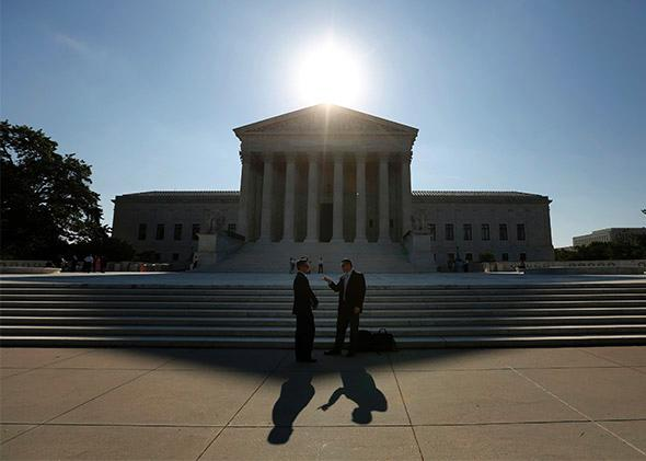 Two men talk as the sun rises over the Supreme Court.