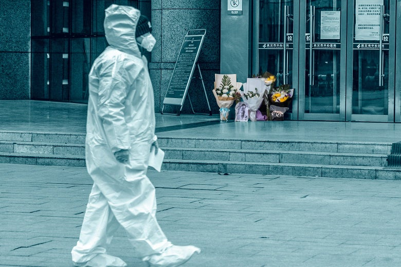 A medical staff member in full-body protective gear walks past a flower tribute on the ground outside the hospital doors
