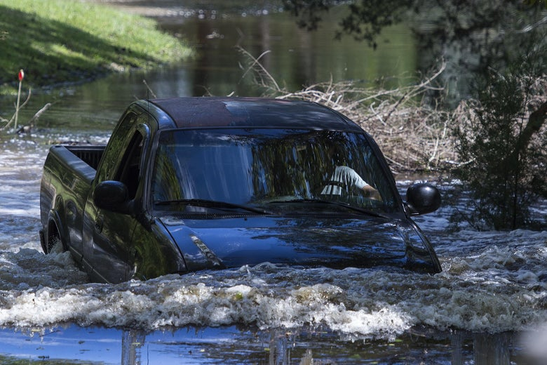 A truck drives through deep flood water in Rhems, North Carolina on September 18, 2018. - Rain-gorged rivers threatened further flooding on the storm-battered US East Coast Monday as the death toll from Hurricane Florence, now a tropical depression, jumped to 31. (Photo by Andrew CABALLERO-REYNOLDS / AFP)        (Photo credit should read ANDREW CABALLERO-REYNOLDS/AFP/Getty Images)
