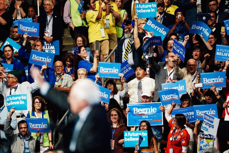 Supporters of Sen. Bernie Sanders stand and cheer as he delivers remarks.