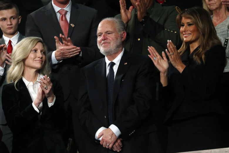 Limbaugh smiles as his wife, Kathryn, and Melania Trump clap beside him.