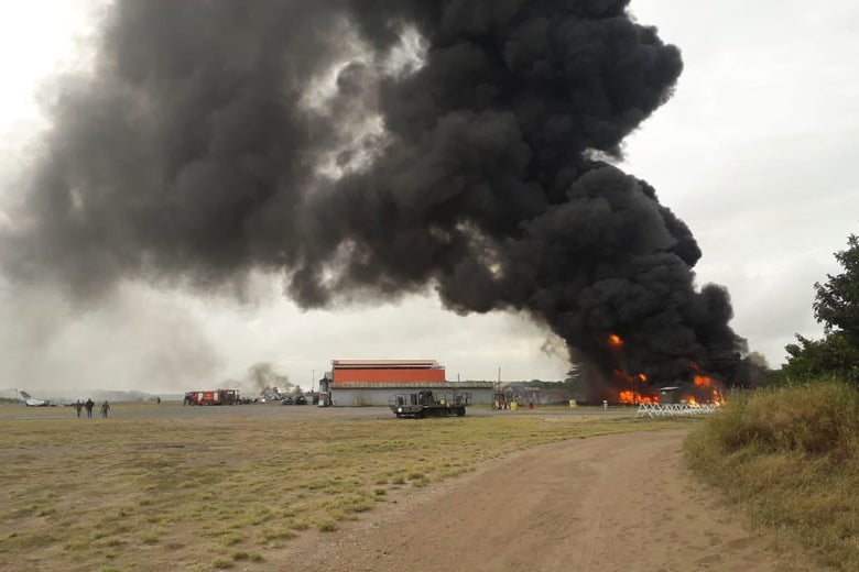 A huge plume of smoke rises from a military base in a grassy area.