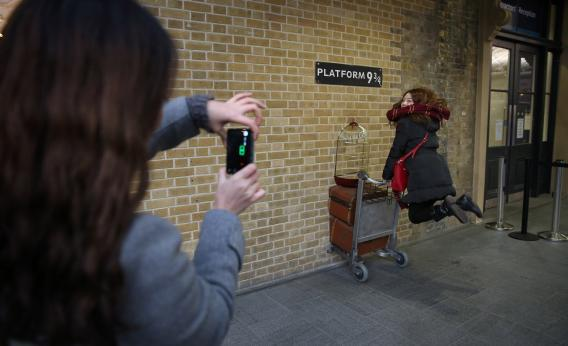 A tourist re-enacts a scene from Harry Potter at King's Cross station