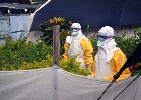 Members of Doctors Without Borders (MSF) wearing protective gear walk outside the isolation ward of the Donka Hospital.
