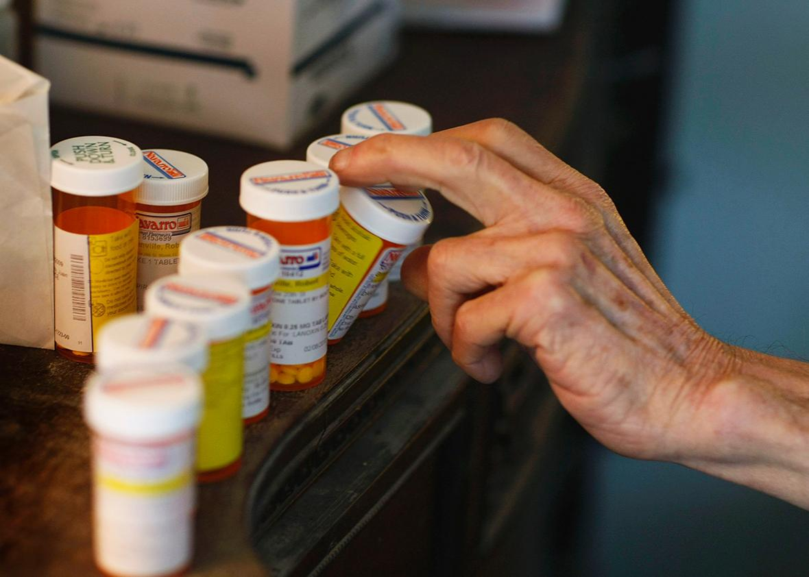 A man reaches for a medicine bottle as he takes his prescription pills on February 25, 2009 in Miami, Florida.